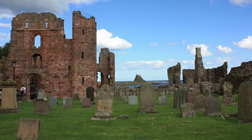 Lindisfarne Priory with Lindisfarne castle in the distance :Photo © 2015 David Simpson