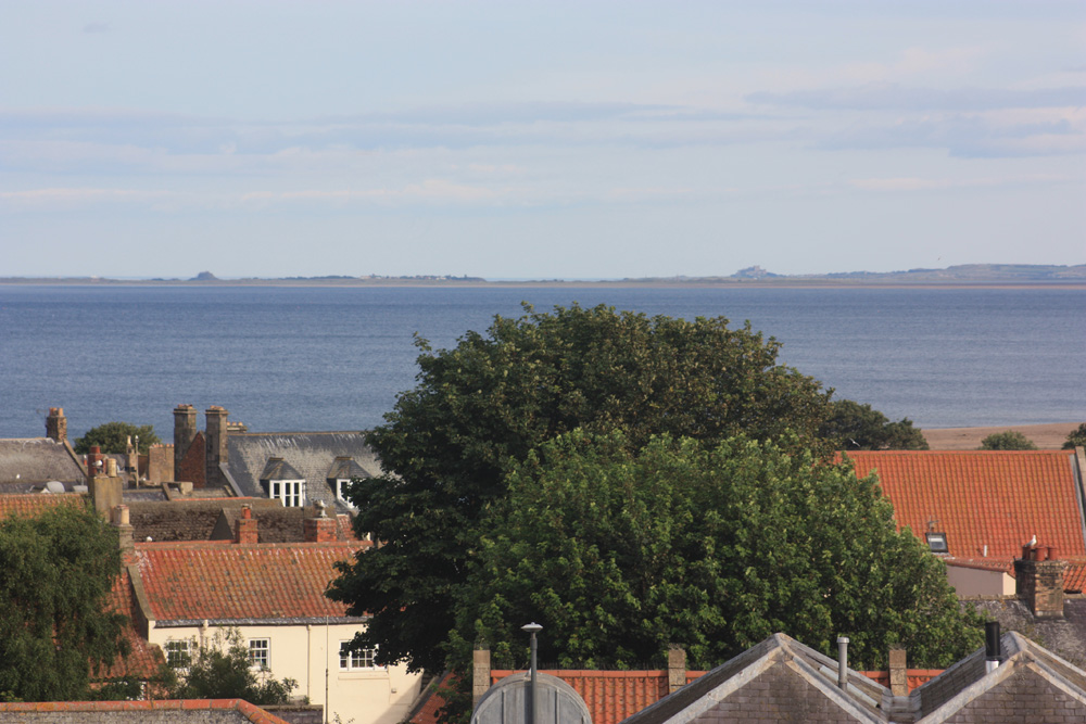 Holy Island and Bamburgh pictured beyond the Berwick rooftops.